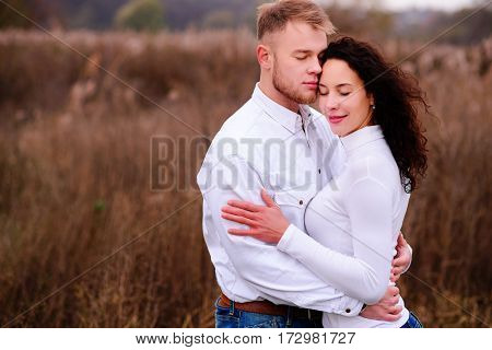 Young Couple Embrace In Autumnal Landscapes With Closed Eyes, Wh