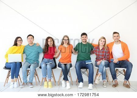 Group of people with books and gadgets sitting near light wall