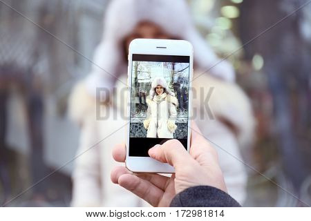 Young man taking photo of beloved girlfriend on the street