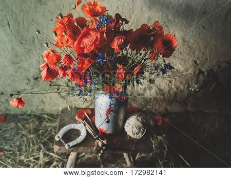a bouquet of poppies and cornflowers in a rustic style