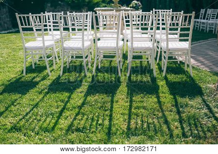 white chairs at the wedding are on the green grass on a sunny day, and the long shadow of them