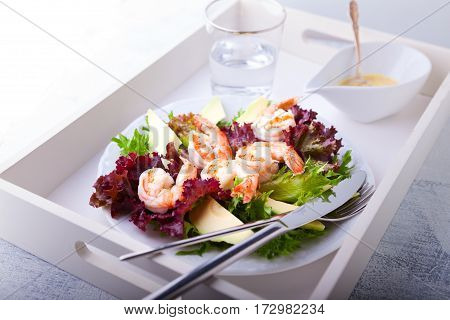 Avocado shrimp salad with mustard sauce on a tray.