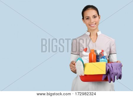 Hotel female chambermaid holding cleaning supplies on color background