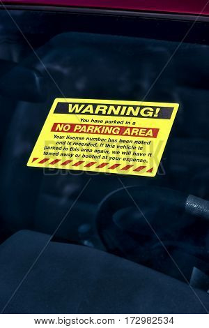 Vertical shot of a Warning Parking Sticker on a car's Windshield.