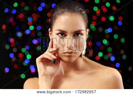 Beautiful woman with holiday makeup against defocused lights