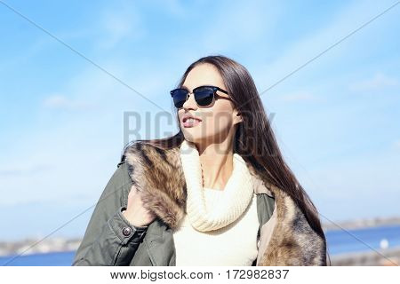 Beautiful young woman at seashore on sunny autumn day
