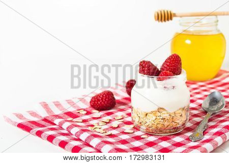 Overnight oatmeal with yogurt and raspberry on the checkered tissue on the white background with copy space