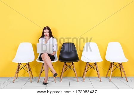 Young woman waiting for job interview on yellow wall background