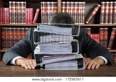 A Male Lawyer Leaning On Stacked Folders On Wooden Desk In Courtroom