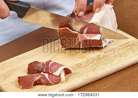 Dry cured ham thinly sliced Closeup on chef hands slices prosciutto Italian delicatessen dishes cooking process