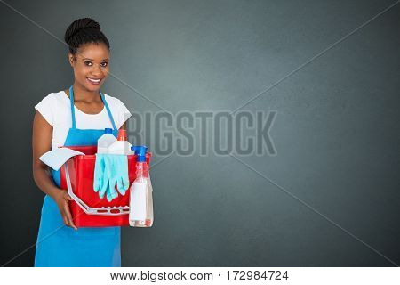 Portrait Of An African Female Janitor Holding Cleaning Equipment On Gray Background