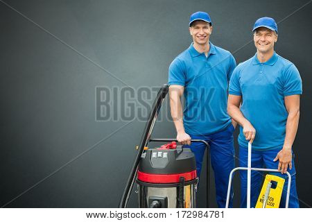 Portrait Of A Two Happy Male Cleaners With Cleaning Equipment Standing On Gray Background