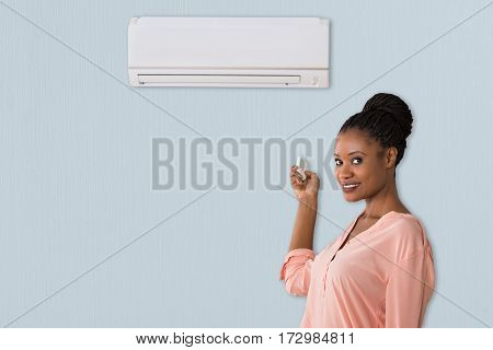 Young African Woman Holding Remote Control In Front Of Air Conditioner At Home