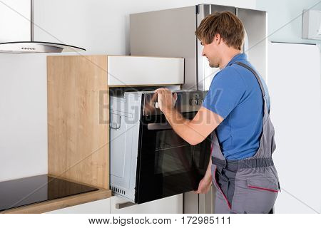 Male Technician In Overall Installing Oven In Kitchen