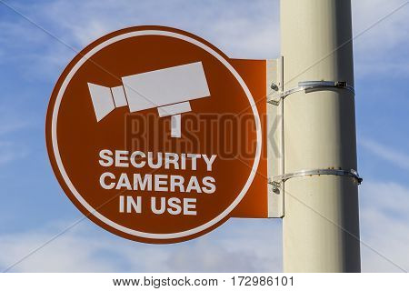 Orange Security Camera In Use Sign on Gray Post and Partly Sunny Background I