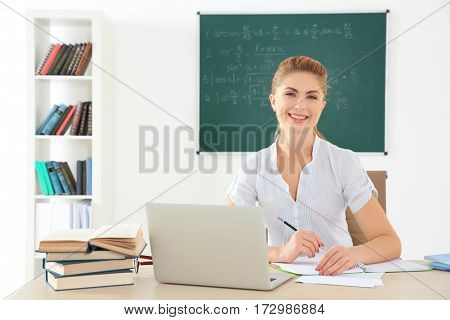 Young teacher at desk in classroom