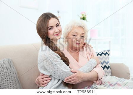 Beautiful girl with grandmother on couch at home