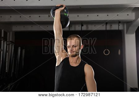 Portrait Of A Young Athlete Man Doing Kettle Bell Exercise In The Gym