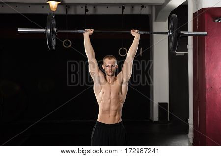 Portrait Of A Young Athlete Man Lifting Barbell In The Gym