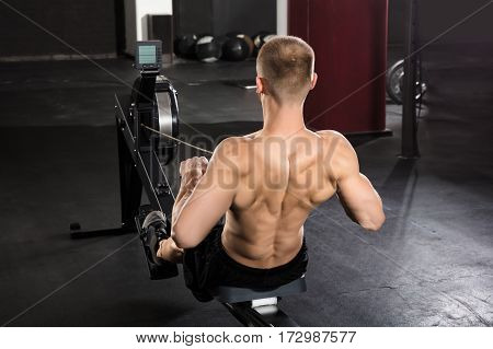 Rear View Of A Young Athlete Man Working Out On Row Machine In Gym