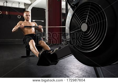 Young Athlete Man Exercising With Row Machine In The Gym
