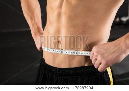 Close-up Of A Muscular Man Measuring Waist Using Measuring Tape In The Gym