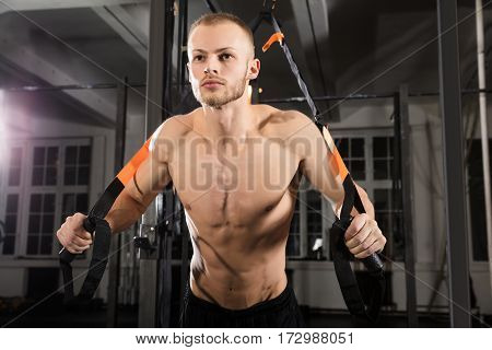 Low Angle View Of A Young Athlete Man Exercising With Suspension Trainer In Gym