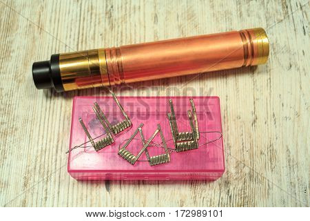 Electronic cigarette parts on the pink box on the table. Vaping.