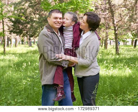 happy family and child in summer park, beautiful landscape with trees and green grass
