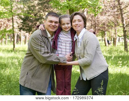 happy family with child in summer park, sunlight, green grass and trees