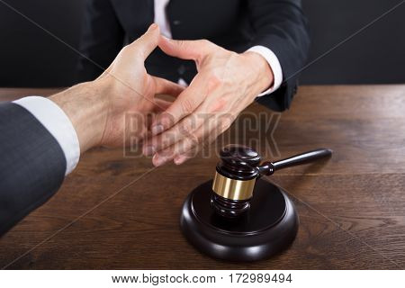 Client And Judge Shaking Hands With Each Other Near Gavel On Wooden Desk