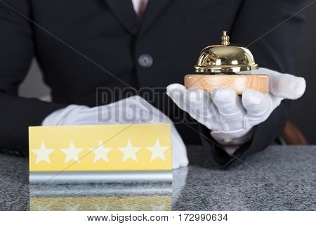 Close-up Of A Waiter Hand Holding Service Bell And Five Star Shape Card On Desk
