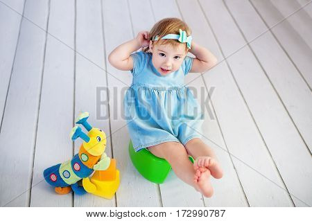 Baby sitting on potty in home interior