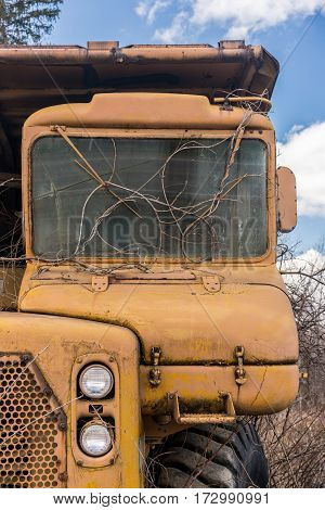 Rusting and overgrown heavy yellow industrial truck and equipment abandoned in economic recession