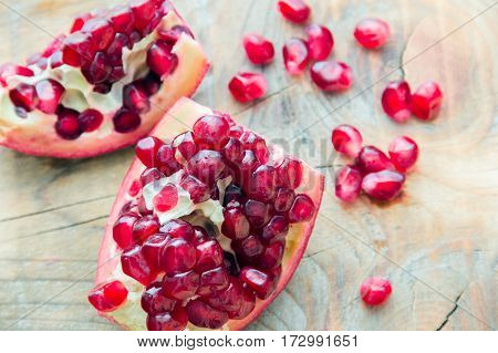two pieces of red pomegranate on the wooden background with scattered grains