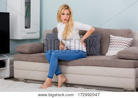 Young Woman Sitting On Sofa Suffering From Back Pain At Home