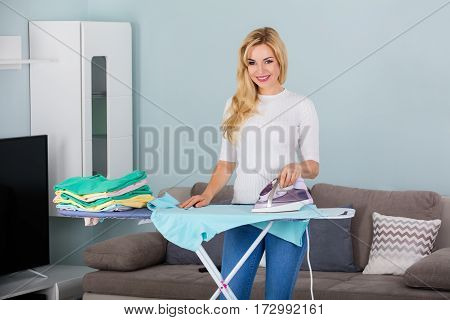 Young Smiling Woman Ironing Clothes On Ironing Board At Home
