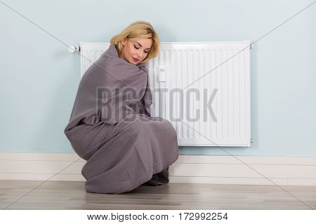 Young Woman With Blanket Suffering From Cold Sitting Near Heating Radiator At Home. Energy Saving Concept