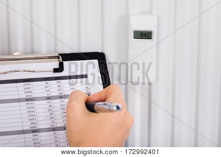 Person Hand Maintaining Records Of Digital Thermostat On Clipboard At Home