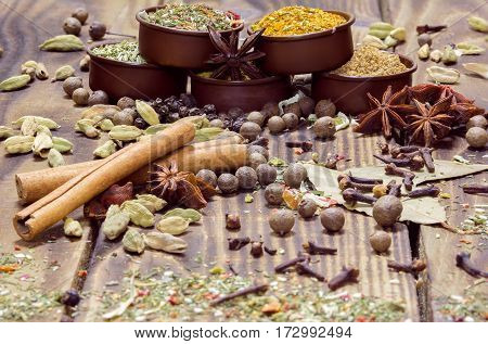 various spices in containers and on a wooden background