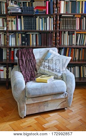 Armchair with book and eyeglasses inside home library interior with large bookshelf in background