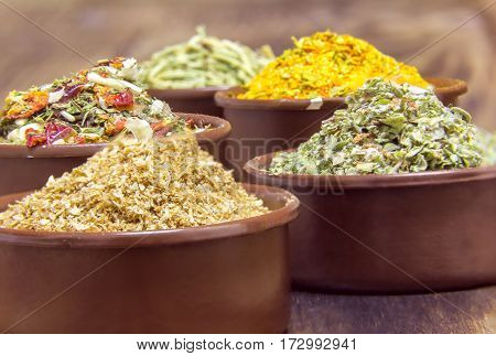 various spices in containers on a wooden background