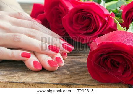 Skin care of a beauty female hands with red nail manicure. And brown wooden background with red roses