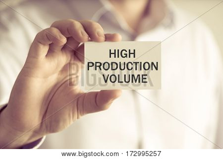 Businessman Holding High Production Volume Message Card