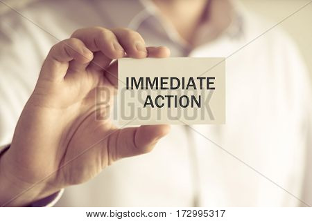 Businessman Holding Immediate Action Message Card