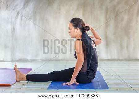 Asian trainee strong woman practicing difficult yoga pose in a concrete background Sport healthy concept