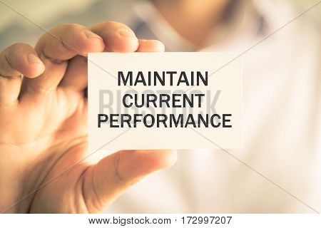 Businessman Holding Maintain Current Performance Message Card