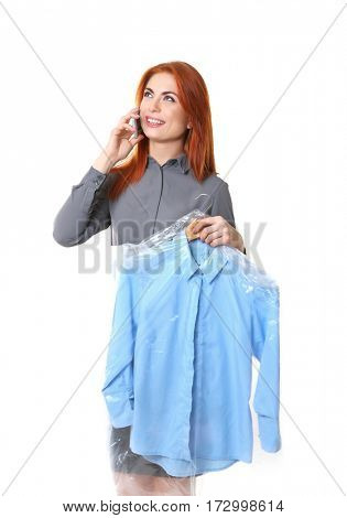 Happy woman holding shirt in plastic carrying case on white background