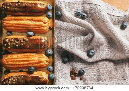 Delicious eclairs in the tray with a napkin