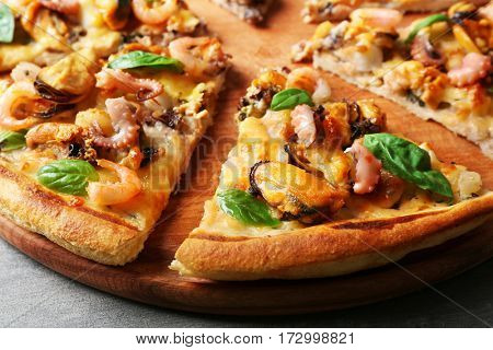 Tasty sliced pizza with seafood, closeup